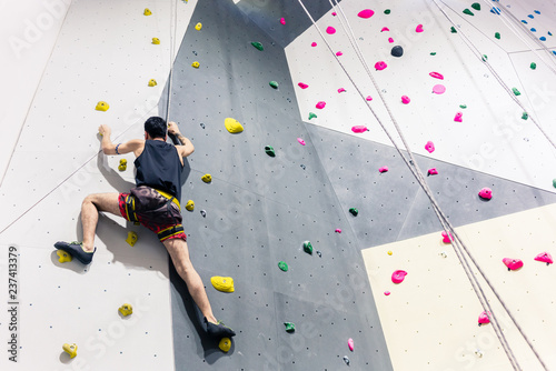 Photo Rear view of man climbing wall with help of grip