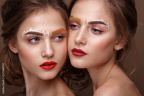 Two girls are twin sisters with an unusual eyebrow makeup Fototapet