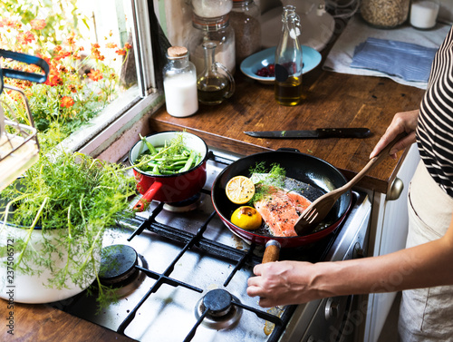 Woman cooking salmon in a pan