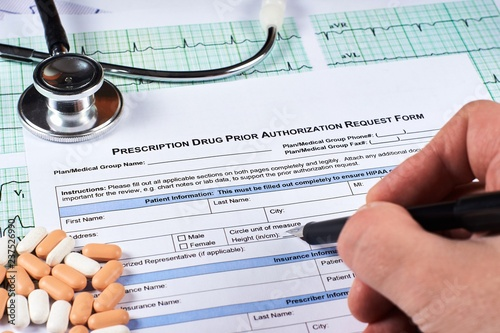 Photo Human fill Prescription drugs prior authorization request form, pills, stethoscope on a EKG graph paper background