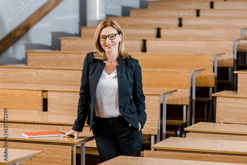 beautiful female university professor smiling and looking at camera in classroom Fototapeta