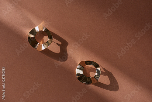 Canvastavla top view of beautiful luxury golden earrings on brown surface with sunlight