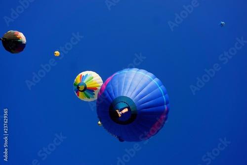 globos aerostáticos en vuelo con cielo azul profundo de fondo