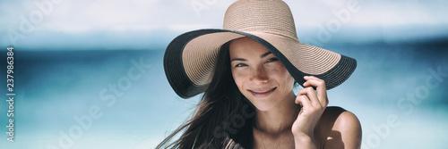 Beach sun tan skin care Asian beauty woman happy on beach vacation panoramic banner wearing sunhat. Healthy suntan skincare concept with hat.