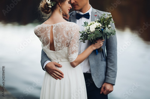 Leinwand Poster Back view of husband embracing his beautiful elegant wife in lace wedding dress with lovely bouquet against unfocused lake surface