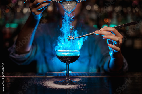 Bartender girl adding to a brown cocktail and pour on a flamed badian on tweezers a powdered sugar in the blue light