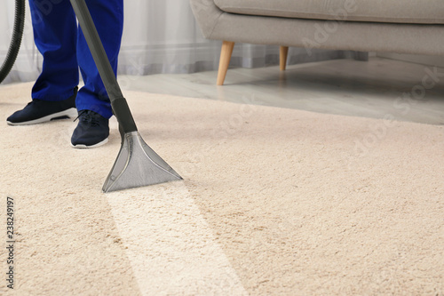 Man removing dirt from carpet with professional vacuum cleaner in room