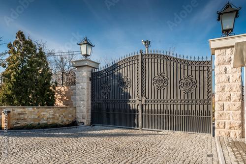 Metal driveway security entrance gates set in brick fence Fototapete