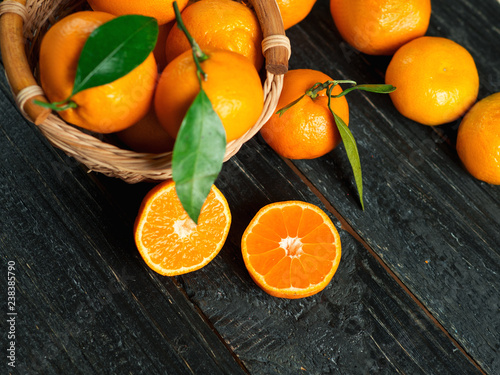 Tangerines in a wooden basket on a dark wooden table