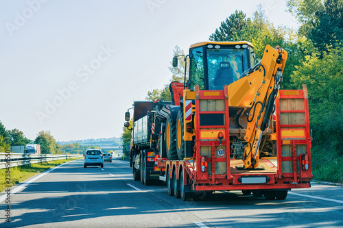 Fotografie, Obraz Truck trailer transporter with hauler carrying tractor road Slovenia