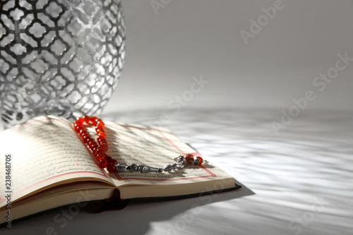 Koran with Muslim prayer beads on table. Space for text
