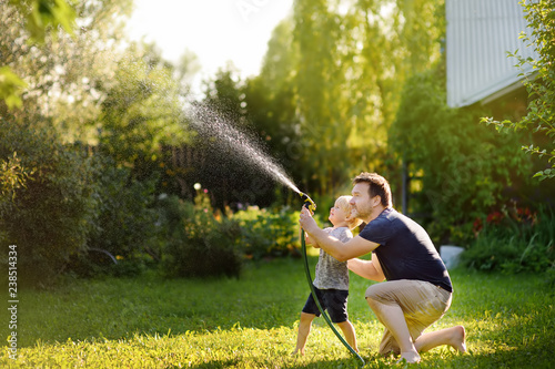 Funny little boy with his father playing with garden hose in sunny backyard Fototapeta