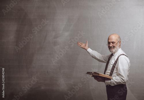 Obraz na płótnie Smiling confident professor teaching and pointing at the blackboard