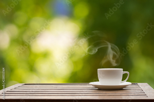 Coffee espresso on wood table nature background in garden,warm tone