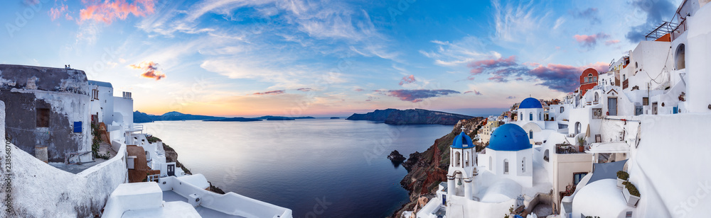 Beautiful panorama view of Santorini island in Greece at sunrise with dramatic sky.