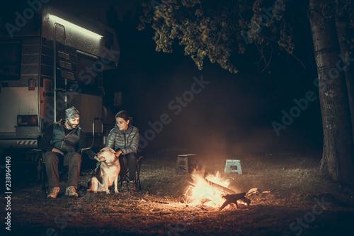 Slika na platnu Couple on vacantion near campfire and motorhome