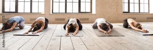 Five girls during yoga session at sport studio. Sportive females lying in row relaxing on wooden floor rubber mats doing Child Pose. Horizontal photography banner for website header. Wellness concept