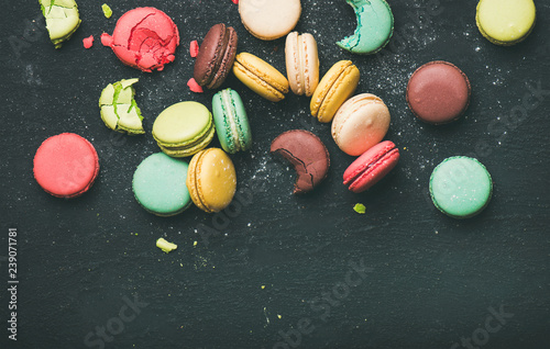 Fototapeta Flat-lay of sweet colorful French macaron cookies over black background, top vie