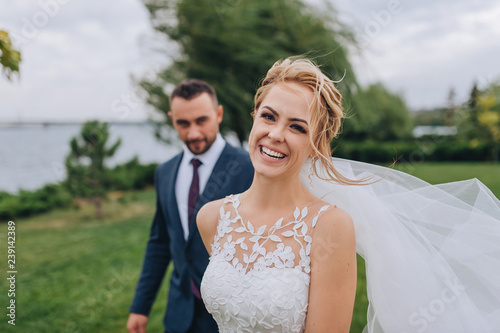 Obraz na plátne Blonde and smiling bride and bearded groom walk, holding hands, in the park with green grass and willows