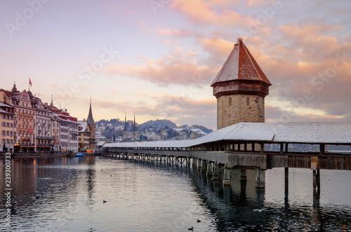 Fototapeta Historic city center of Lucerne with view of famous wooden bridge Kapelbrücke (Chapel Bridge) on river Reuss, stone tower Wasserturm