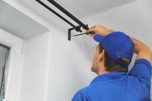Cuadros en Lienzo handyman services - worker installing window curtain rod on the wall