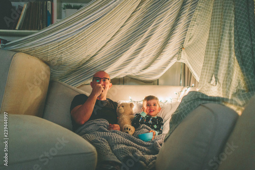 Fototapeta A father and son watching a movie in a fort and eating popcorn.