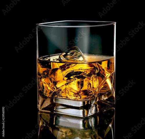 Stylish glass of whiskey with ice on black background