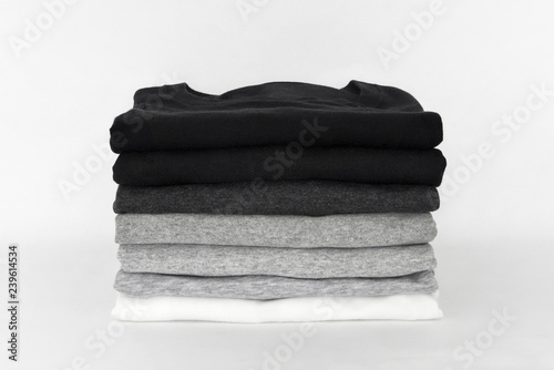 stack of folded black, grey and white color (monochrome) t-shirt on white background