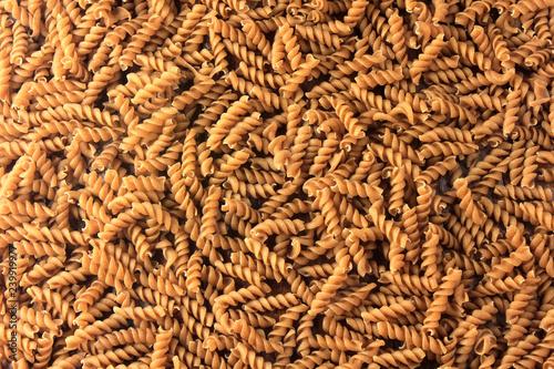 Fotografia Top view Wholemeal pasta fusilli raw organic whole grain on a rustic wooden