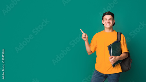 Photographie Teen student with books pointing on copy space