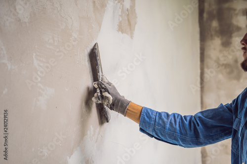 Fotografering master is applying white putty on a wall and smearing by putty knife in a room o