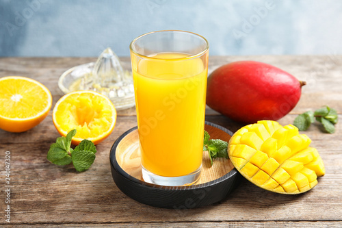Glass of fresh mango drink and tropical fruits on wooden table