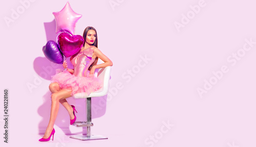 Beauty fashion model party girl with heart shaped air balloons posing, sitting on chair. Birthday party, Valentines Day. Beautiful young brunette woman full length portrait