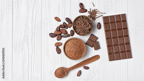 Fotografie, Obraz Tasty chocolate bar with cocoa beans and bowl of chocolate chips and cacao powde