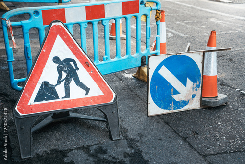 Under construction board sign on the closed road with arrow sign and traffic cone. Caution symbol under construction, work in progress sign.