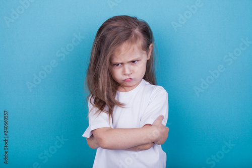 Fotografia The little girl on a blue background was offended by folding her arms and frowni