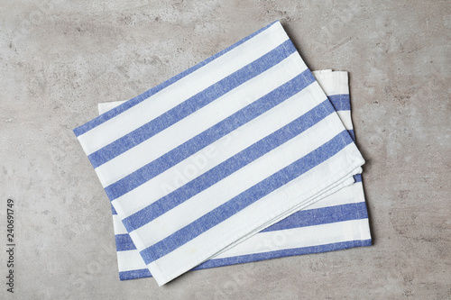 Striped fabric napkins on gray background, top view