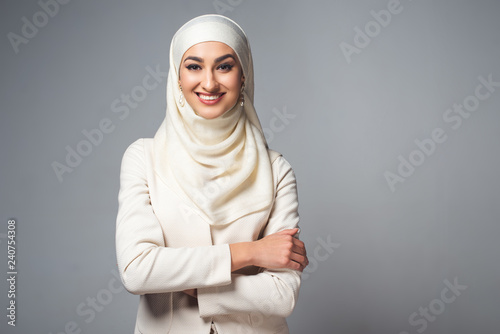 Canvas Print young muslim woman standing with crossed arms and smiling at camera isolated on