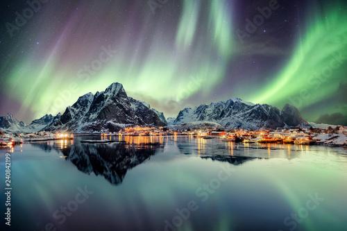 Canvas Print Aurora borealis dancing on mountain in fishing village
