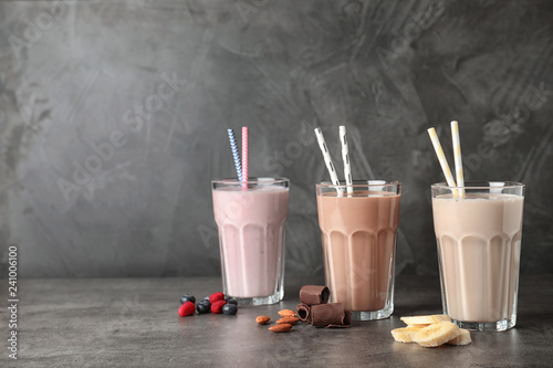 Glasses with different protein shakes and ingredients on table against grey background. Space for text