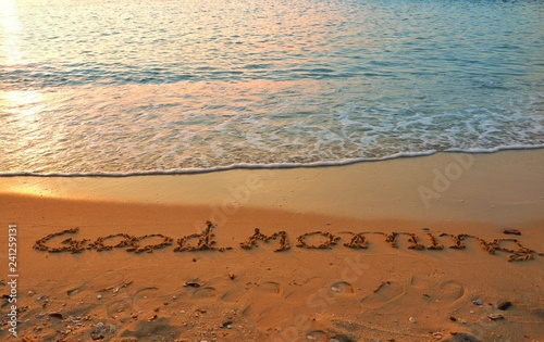 The word of good morning writing on sand beach with waves blue ocean Fototapeta