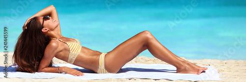 Suntan bikini woman sun tanning on beach - Asian sexy body model lying down on beach towel on perfect blue ocean water background banner panorama.