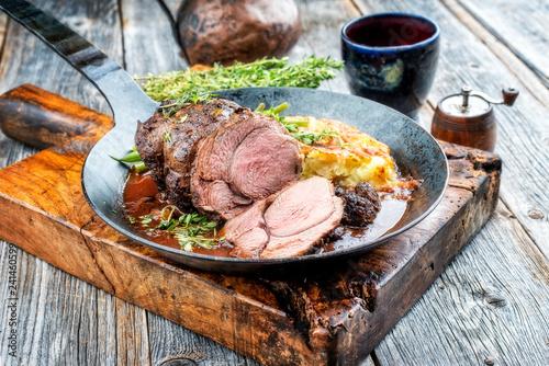 Barbecue Wildschein Braten von der Keule mit schweizer Rösti und Wild Sauce mit Rotwein als Draufsicht in einer schmiedeeisernen Pfanne