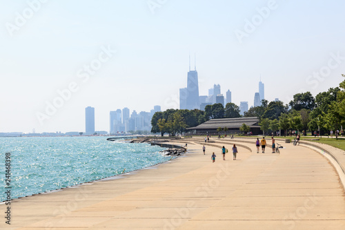 Canvas Print People walking along the shoreline in Chicago, Illinois on a sunny summer mornin
