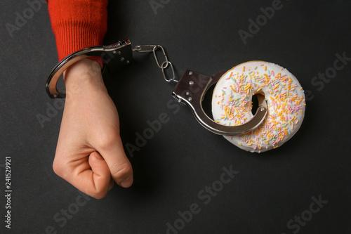 Valokuva Woman handcuffed to tasty doughnut on dark background