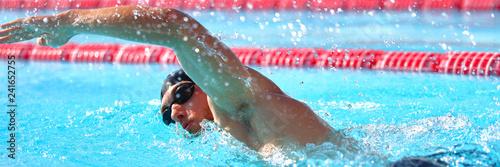 Swimmer man athlete swimming in pool lanes doing a lap. Swim race in crawl. Banner panorama crop.