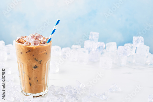 Leinwand Poster Summer drink ice coffee with cream in a tall glass with straw surrounded by ice on white marble table over blue background