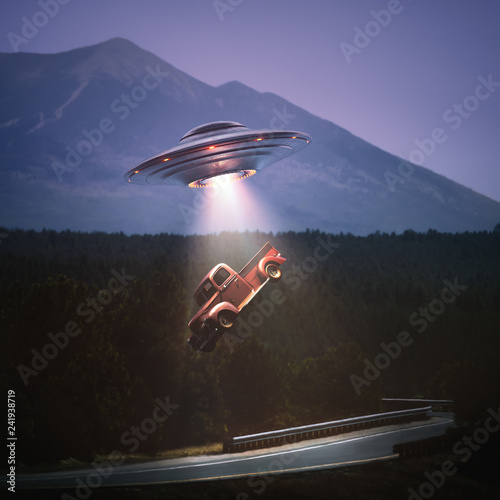 Leinwand Poster Unidentified flying object lifting a car from road