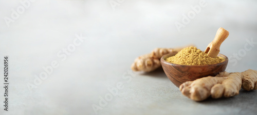 Fotografiet Ginger root and ginger powder in wooden bowl over grey concrete background with copy space