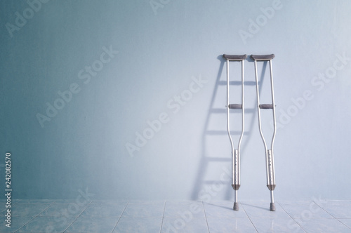 Valokuva Success concept with crutches in the shadow of ladder.